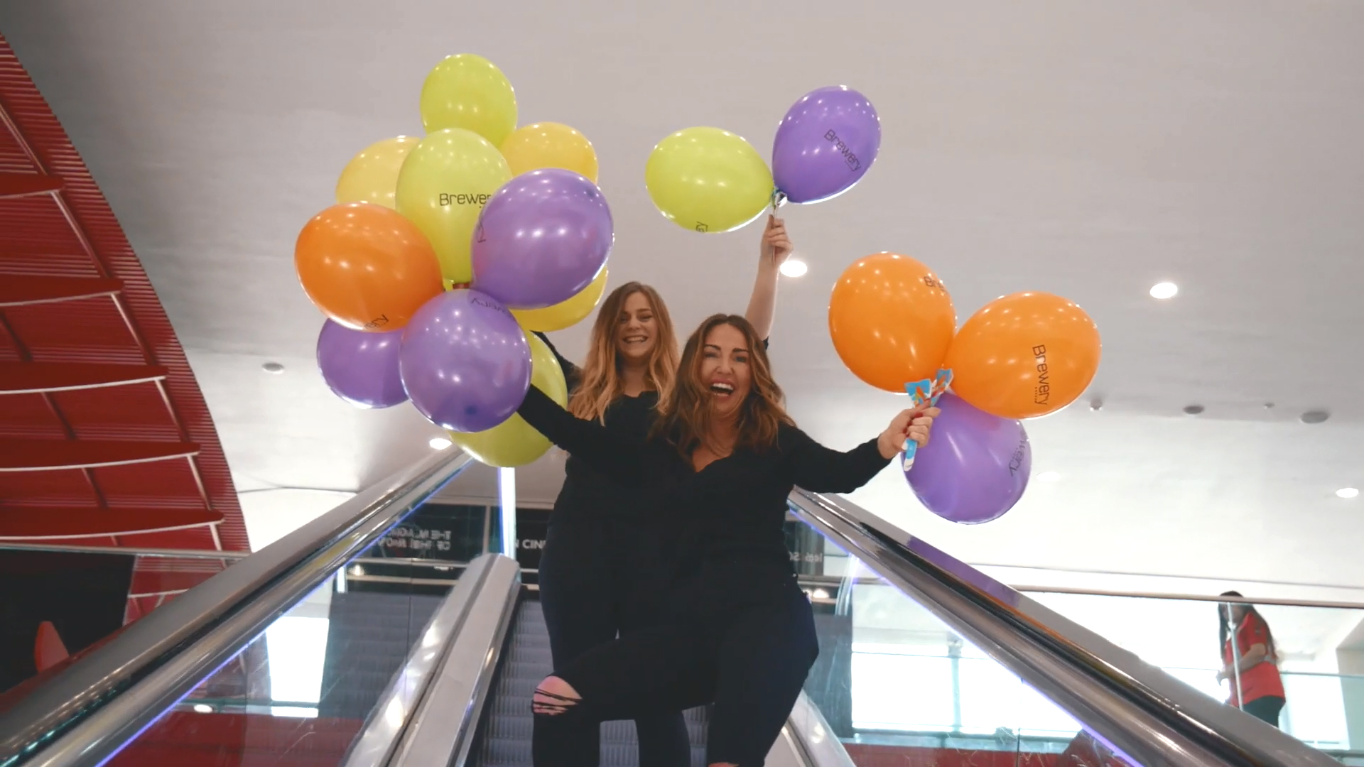 Women Holding Bunches of Branded Balloons on BalloonGrip